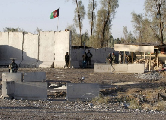 Afghan security forces stand guard at the entrance gate of Kandahar Airport where Taliban stormed on late Tuesday, in Kandahar, Afghanistan